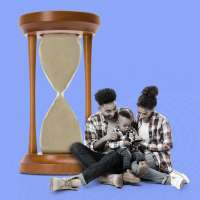 Mother and Father with 1 year old son sitting in front of an oversized hourglass that is completely full of sand