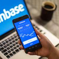 Coinbase logo is seen displayed on a smartphone and a laptop in the background
