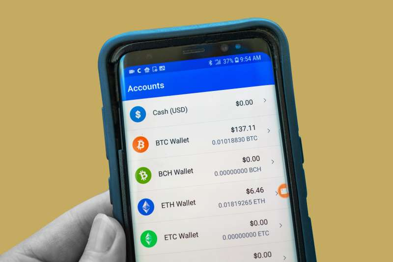 Close-up of hands of a man viewing balances of Bitcoin, Ether and other cryptocurrencies in a wallet app
