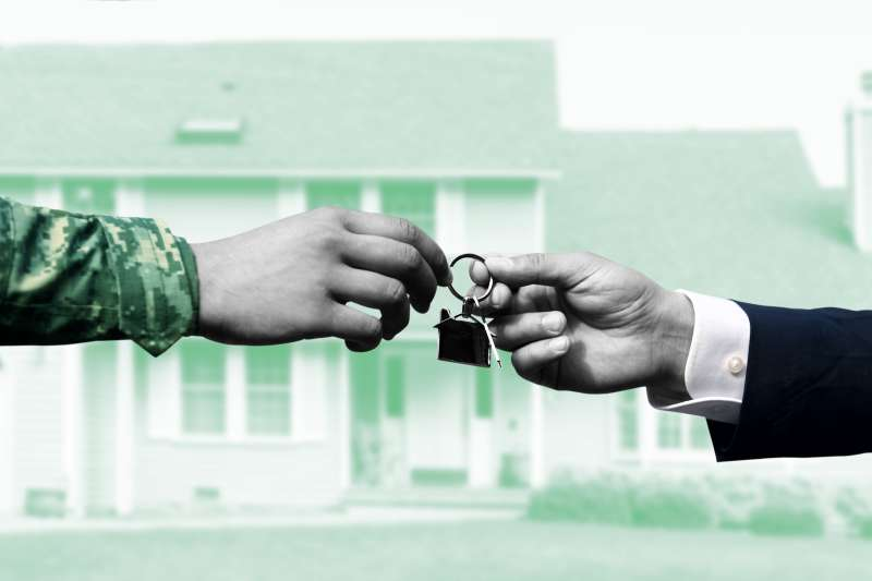 A person handing a military man house keys and a home in the background.