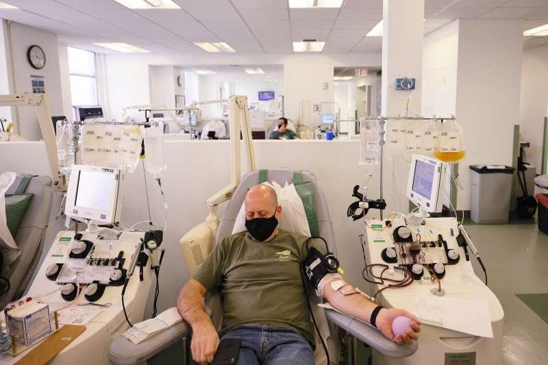 A man donating plasma at a blood center