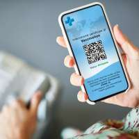 Woman traveling with Covid-19 Vaccine Passport on smart phone