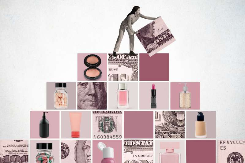 Woman lifting the final block on top of a pyramid made out of money and cosmetic products.