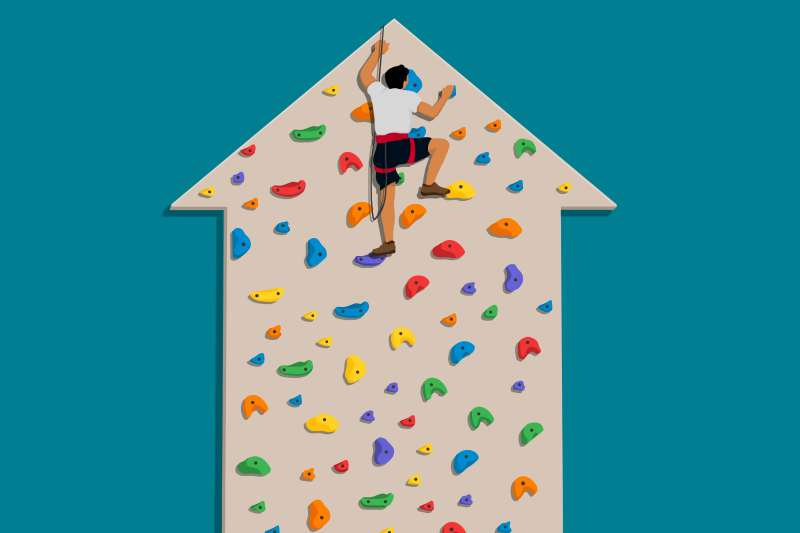 A person climbing to the  peak  of a climbing wall shaped like an upward trending arrow, with no where to go but down