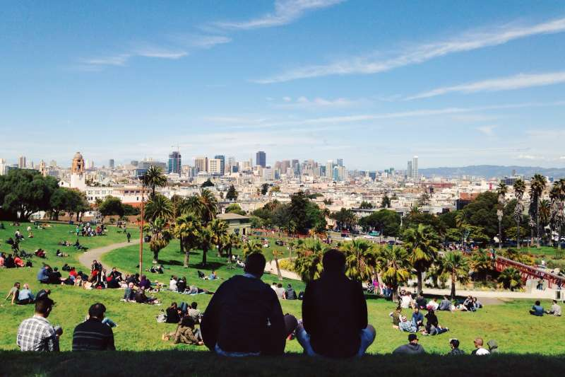 People sitting in a Park with the San Francisco Cityscape in the background
