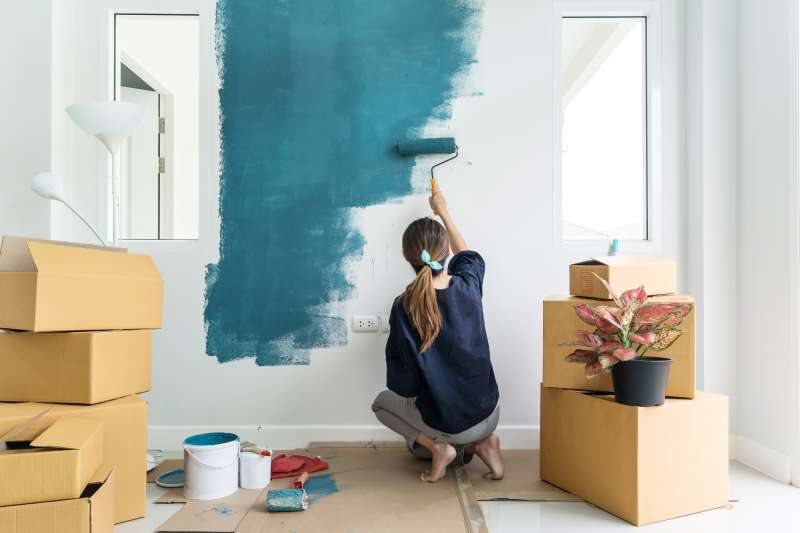 Young woman painting interior wall with a paint roller