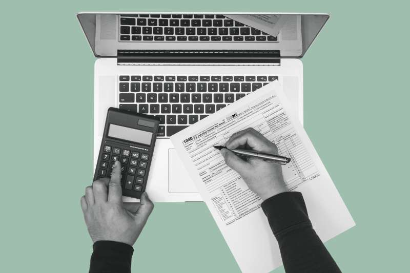 Person filling out a 1040 Tax form with a calculator