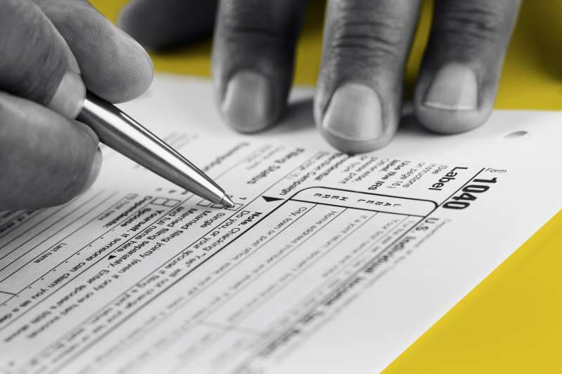 Close up of hands filling out a 1040 Tax Form
