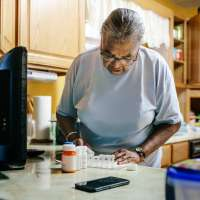 Senior black woman standing in kitchen sorting her medication for the week.