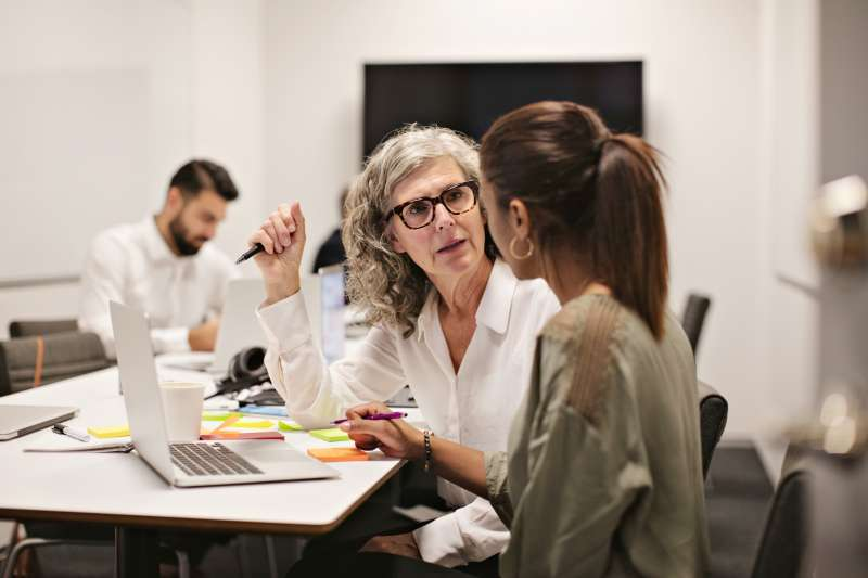 Older businesswomen discussing work over laptop with co-worker