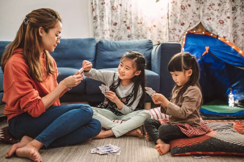 Woman playing cards in her living room with her two daughters