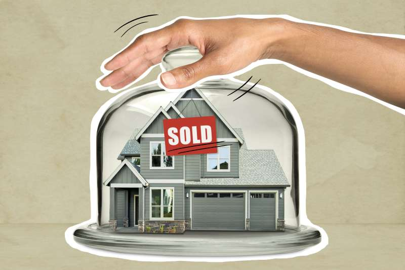House with a sold sign inside a glass cake-stand with a hand holding down the lid
