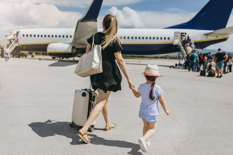 Young mother and her daughter boarding a plane