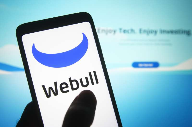 Smartphone displaying the Webull logo with the company's website in the background