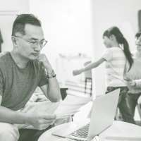 Man reading a letter with his wife and daughter in the background