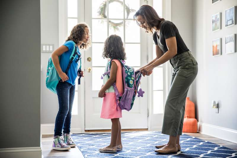 Mother packing daughters backpacks for school