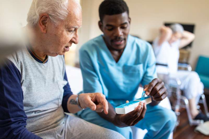 Male nurse giving instructions to senior patient when to take his pills in nursing home