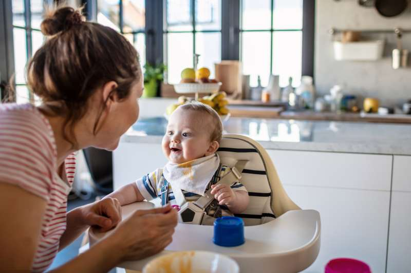 Mother feeds her baby son in high chair at home
