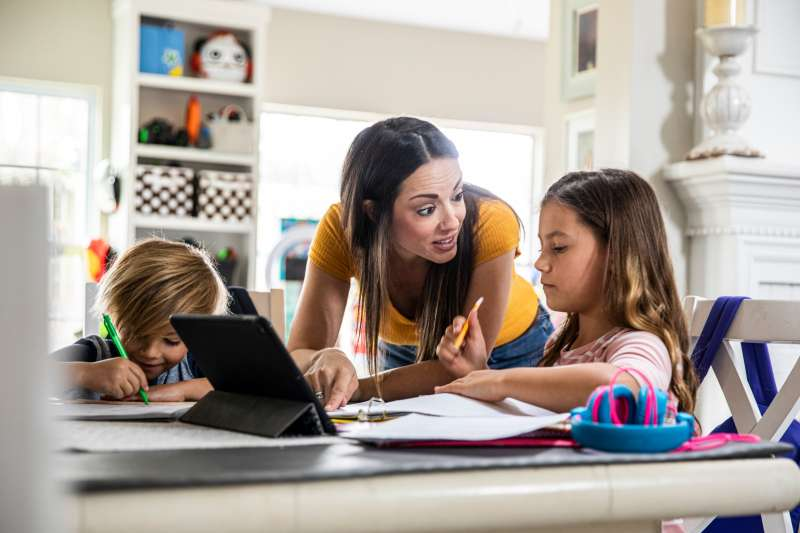Mother working from home and homeschooling children