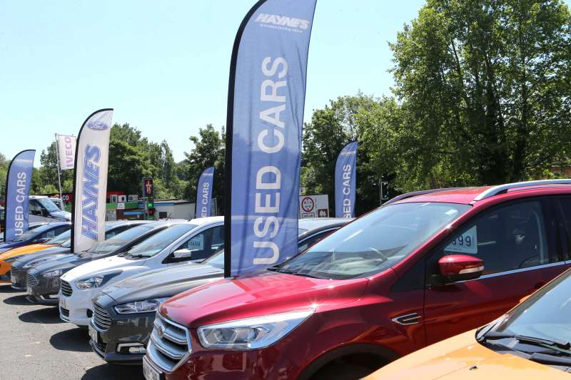 Photograph of a row of used cars for sale.