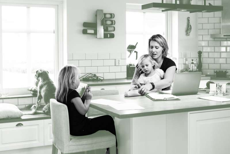 Mother with two daughters sitting at the kitchen counter.