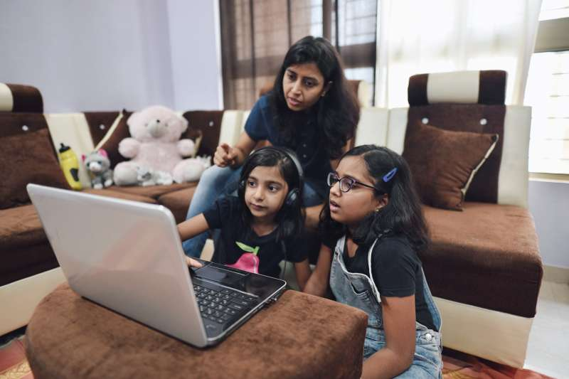 Sisters using a laptop with their mother's assistance