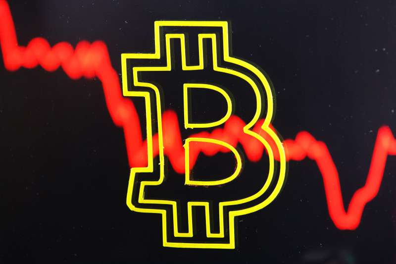 Bitcoin cryptocurrency sign with red crash line behind.