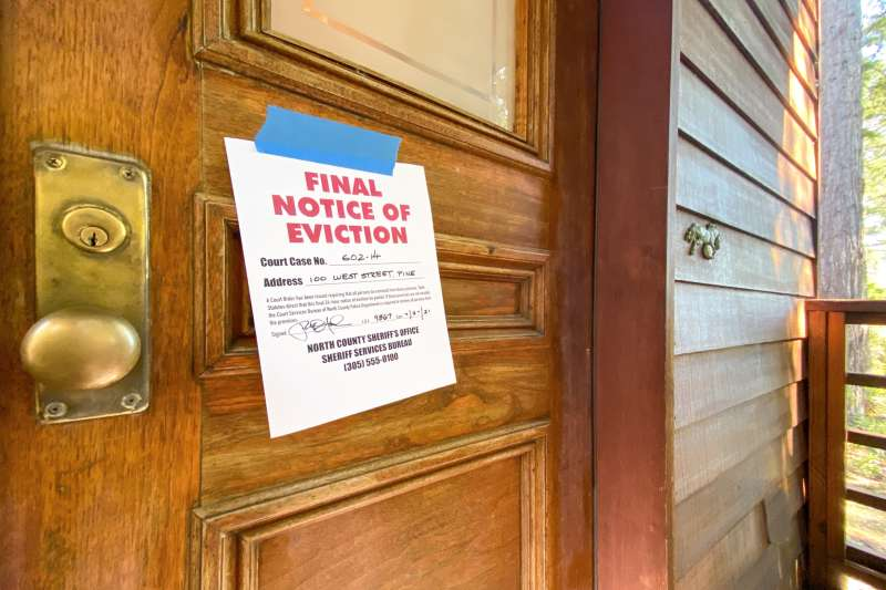 A door with a  Final Notice of Eviction  sign taped to it