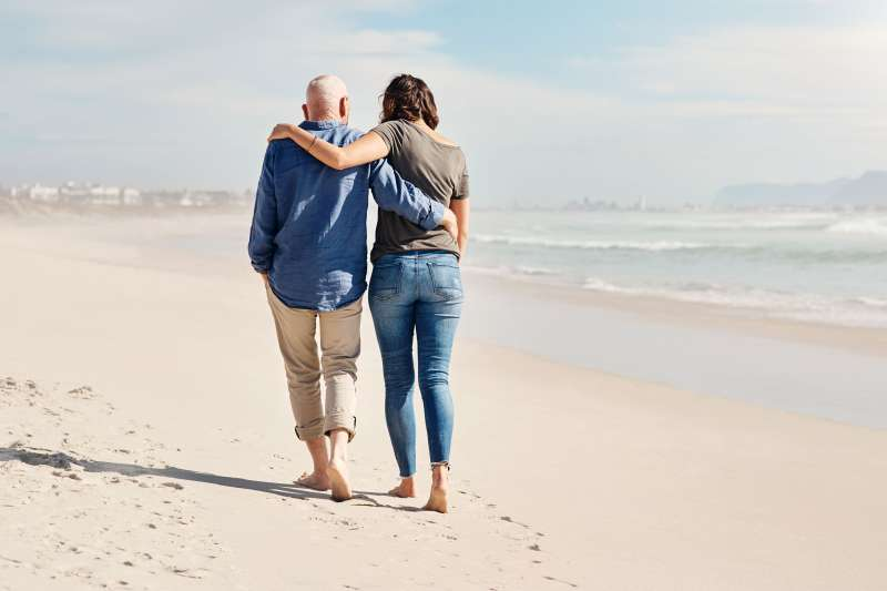 Elderly Father With Adult Daughter Walking Near The Shore