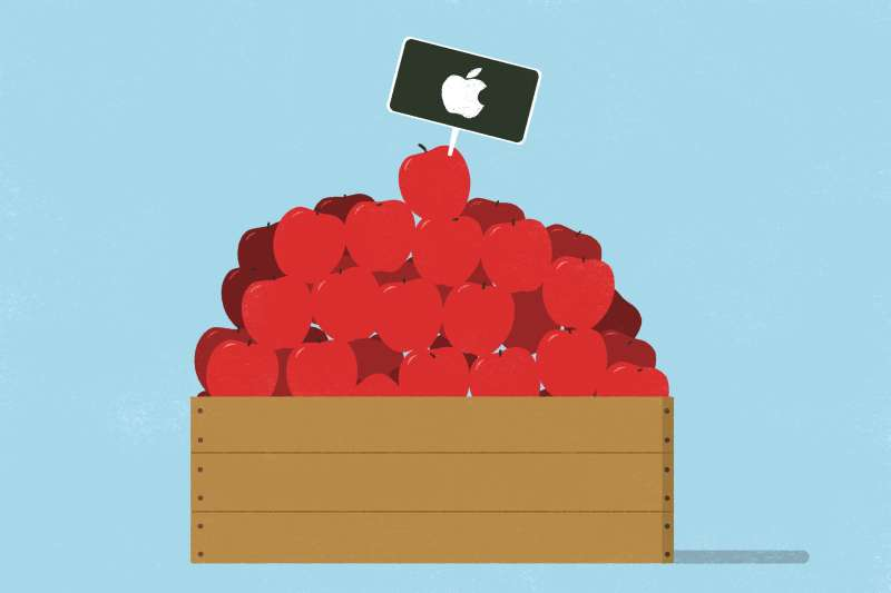 An apple wooden crate fills with apples, with apple stock logo stick on one of them.