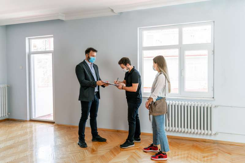 Home Inspector walks through an empty home with a young couple