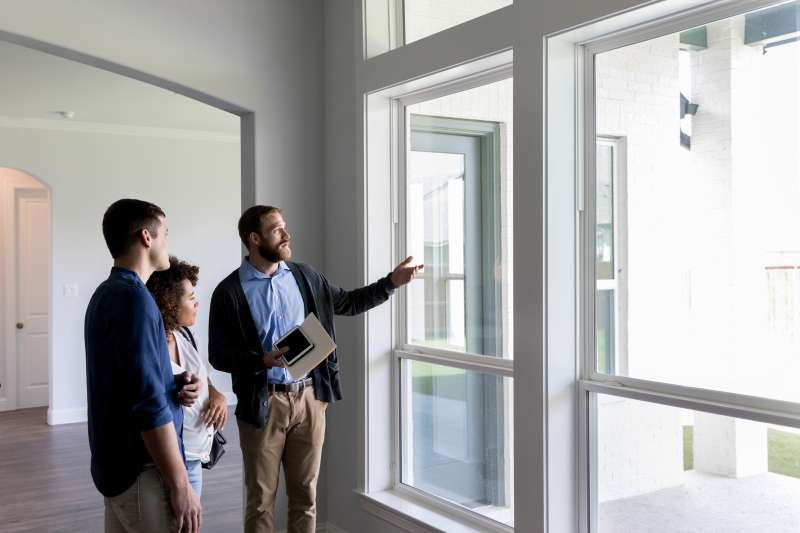 Real estate agent gestures toward a beautiful view out the window of a new home to a potential buyer