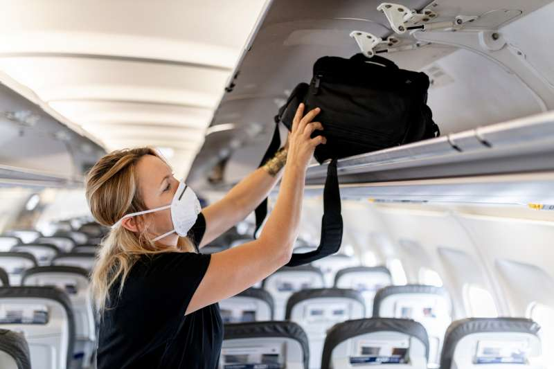 Female passenger wearing a face mask while putting luggage away in the overhead bin on plane