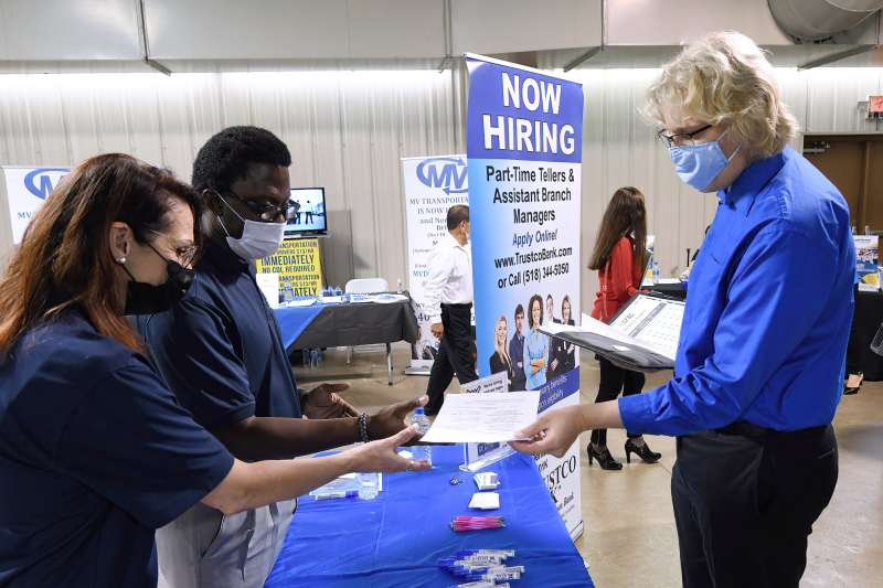 A man hands his resume to an employer at a Job Fair