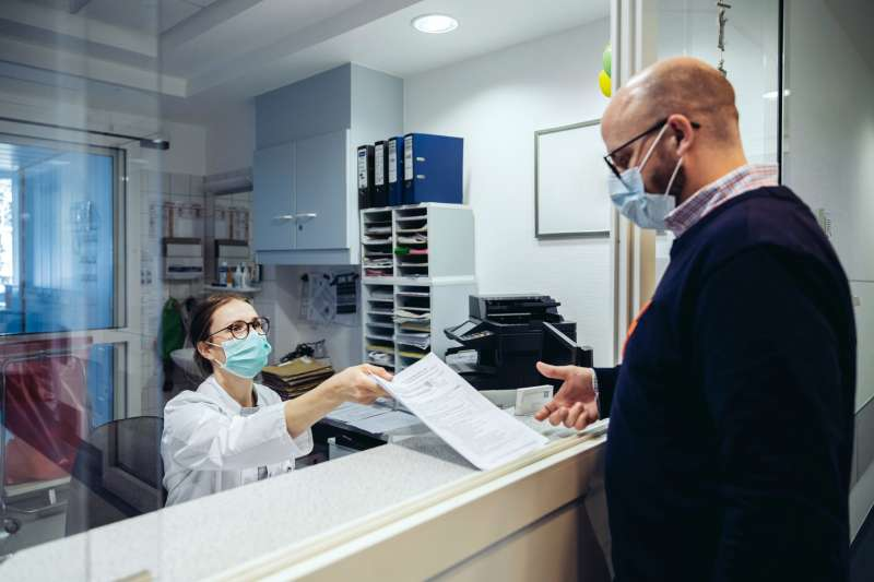 Employee at reception desk of hospital handing over a medical form to a visitor