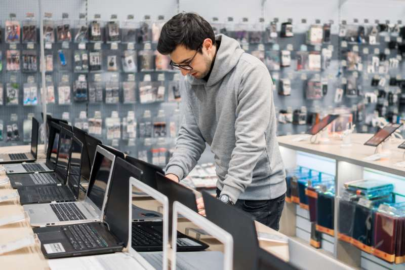 Young male choosing a laptop at electronic store