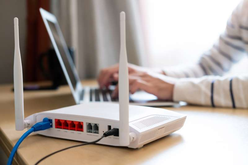 Internet router on a desk with a person working on their computer in the background