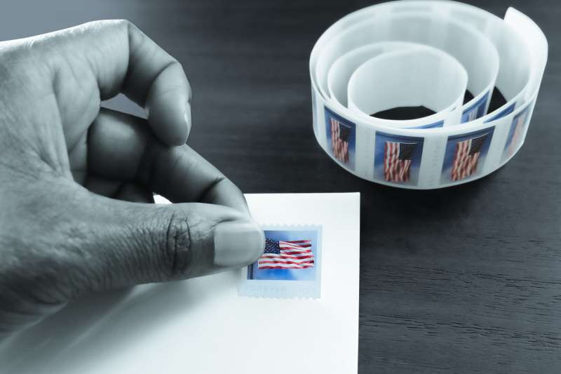 Close-up of a hand placing a stamp with the United States flag on a white envelope.