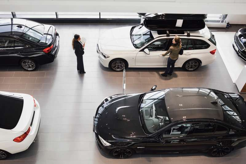 High angle view of saleswoman and customer looking at car in showroom