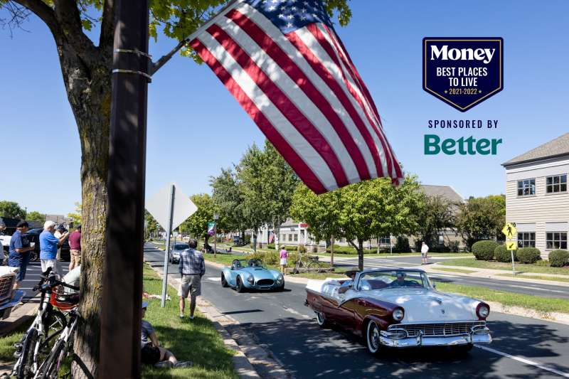 Old cars drive down a street in a car parade in Chanhassen, Minnesota