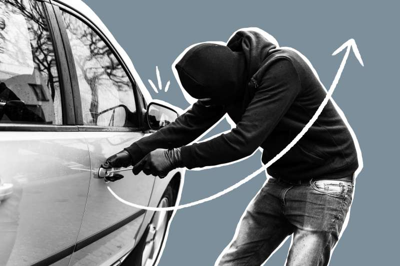 Closeup of a man breaking into a car with a screwdriver
