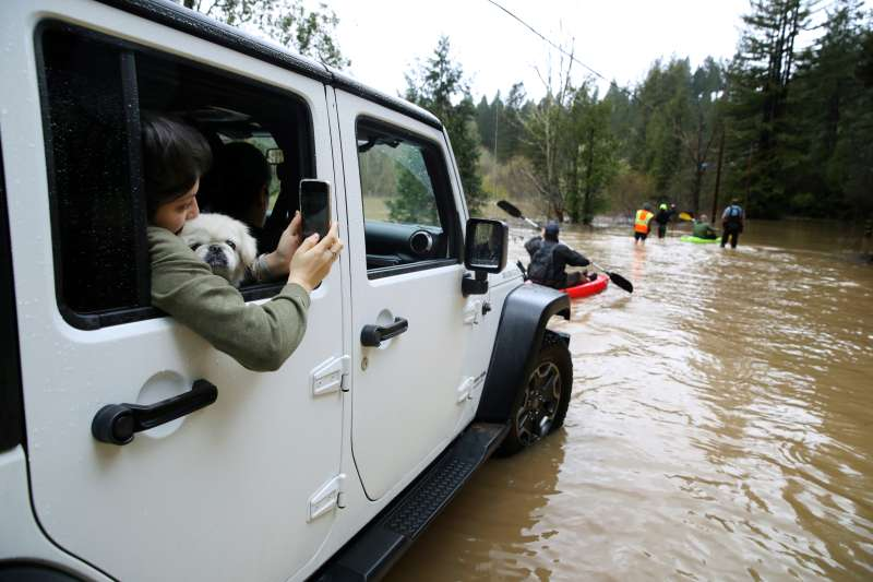 Residents attempt to navigate a flooded section of highway 116 on February 27, 2019 in Guerneville, California