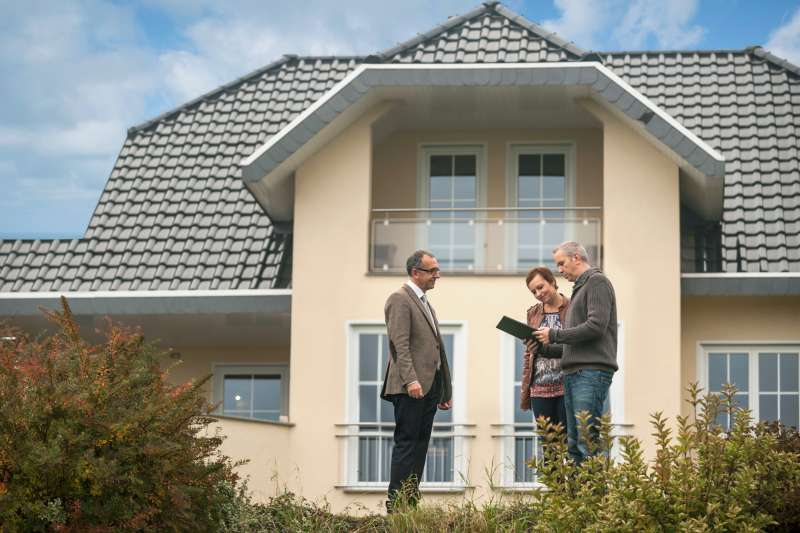 Real estate agent with potential buyers in front of residential house