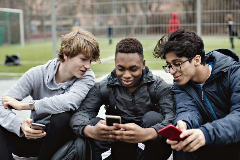 Three teenage boys looking at their smartphones