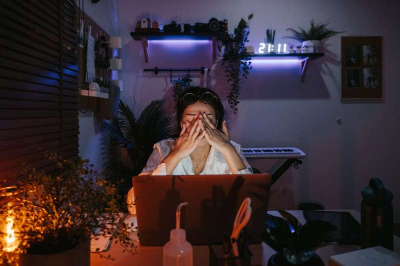 Woman closes her eyes while working late on her computer in a dark room with a clock that reads 21:11 hours.
