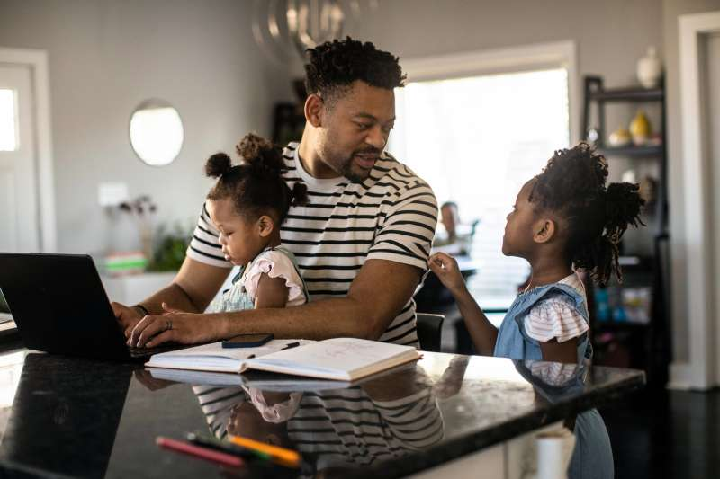 Father multitasking working from home while holding toddler and talking to his older daughter