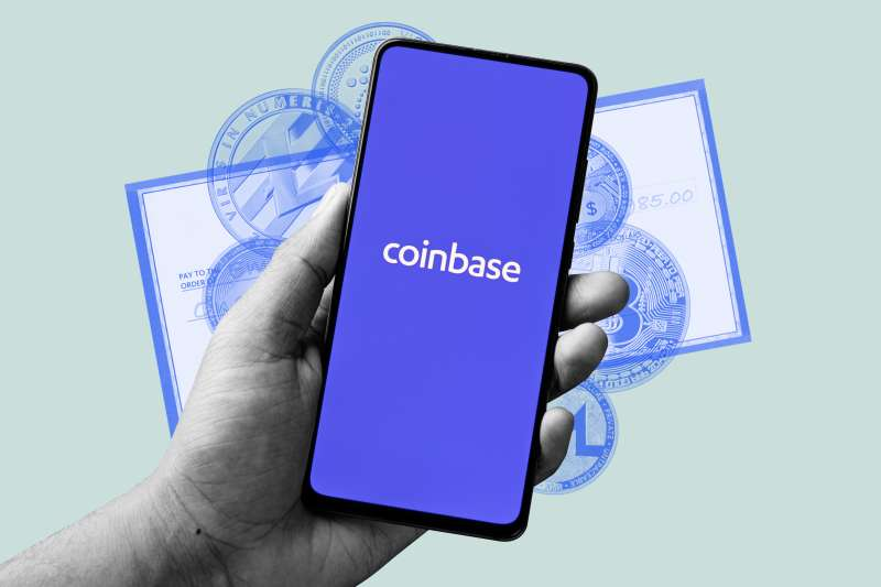 A hand holding a smartphone with the coinbase app open, and a paycheck and multiple crypto currency coins in the background