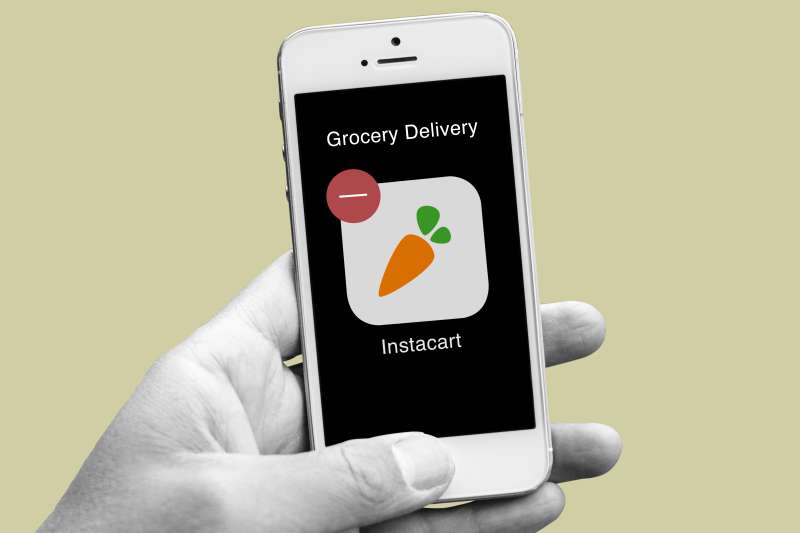 A closeup of a hand with a smartphone showing the Instacart app icon with a delete sign on the top left corner