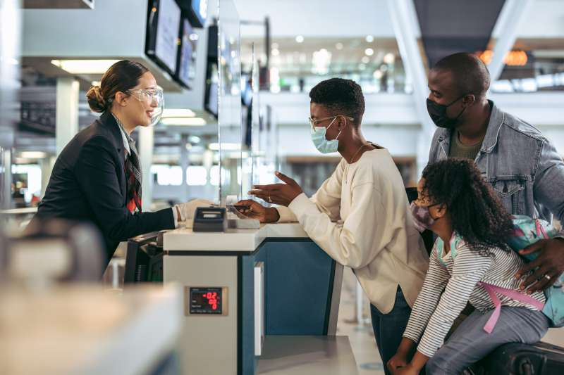 Family of three hand in their passports at the airport check-in desk