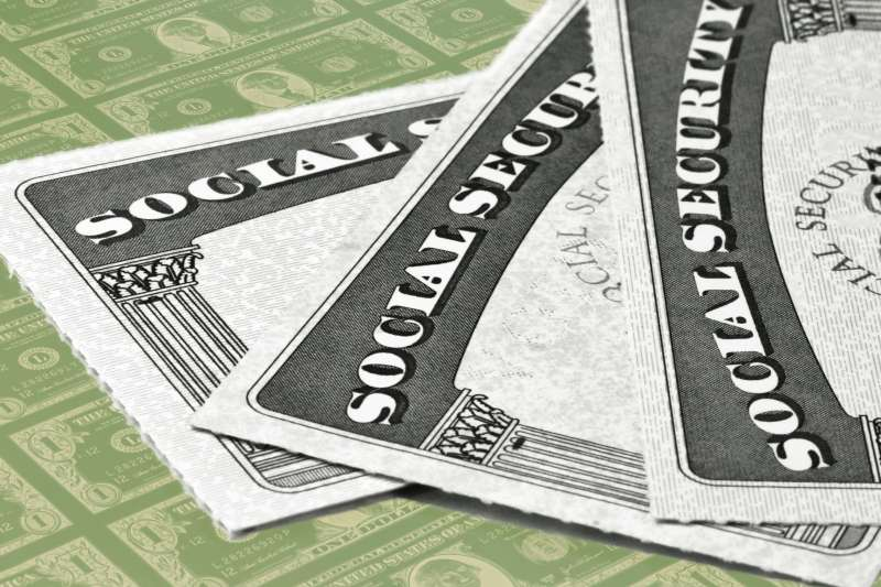 Close-up of three Social Security Cards stacked on top of each other, with one dollar bills in the background